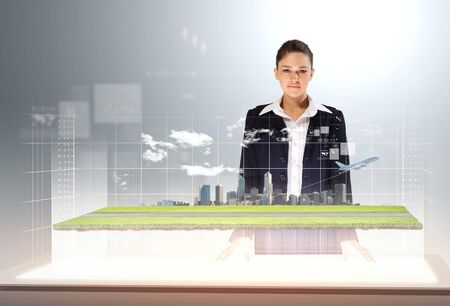 Image of young businesswoman standing against high-tech picture of airplane photo