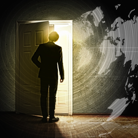 Image of young businessman opening door with light photo
