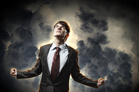 amok: biznesmen w gniewie z zaciśniętymi pięściami, patrząc w niebo