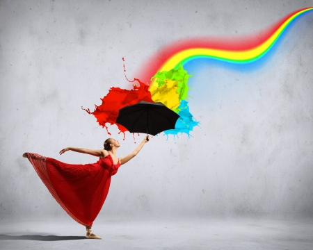 ballet dancer in flying satin dress with umbrella and a rainbow