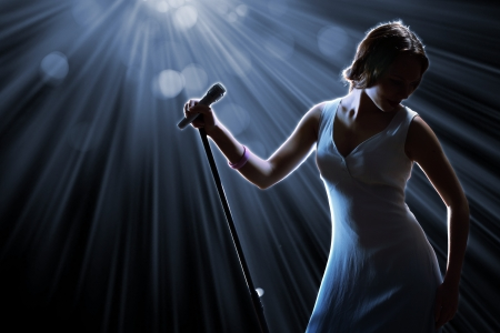 life stages: Female singer on the stage holding a microphone