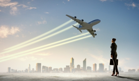 TAKEOFF: Image of business woman holding suitcase looking at airplane in sky