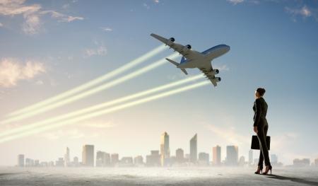 takeoff: Immagine di donna d'affari azienda valigia guardando aereo nel cielo