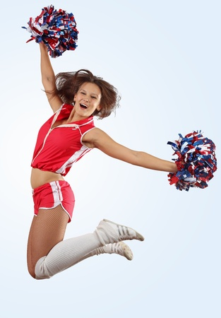 cheerleading: Uniformed cheerleader jumps high in the air isolated on white  Stock Photo