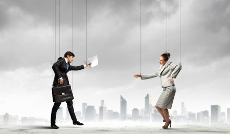 manipulate: Image of businesspeople hanging on strings like marionettes against city background  Conceptual photography