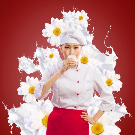 Asian female cook against milk splashes in red apron against flower background drinking milk photo