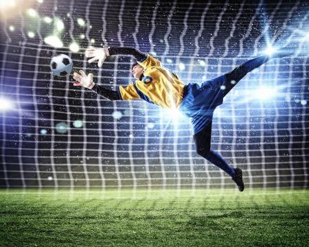 goal keeper: Keeper vangt de bal op het stadion, in de schijnwerpers Stockfoto