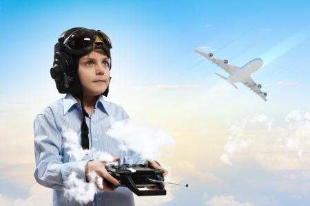Image of little boy in pilots helmet playing with toy radiocontrolled airplane against clouds background photo