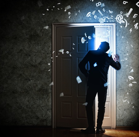 Image of young businessman standing with back opening door photo