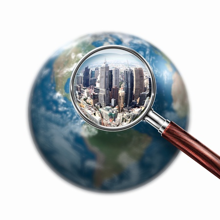Conceptual mini planet with skyscrapers on it under a magnifying glass photo