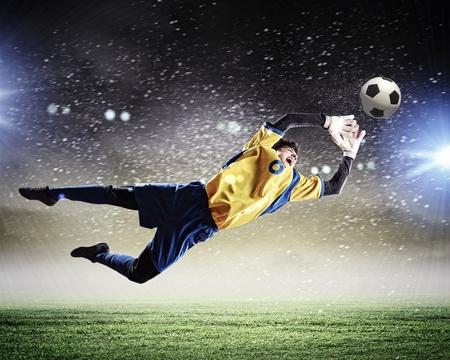 pasto sintetico: Portero coge el bal?n en el estadio, en el punto de mira