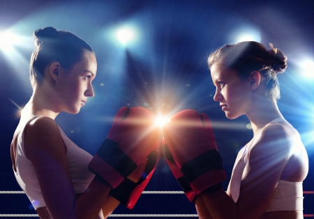 girl fighting: Two young pretty women boxing in ring
