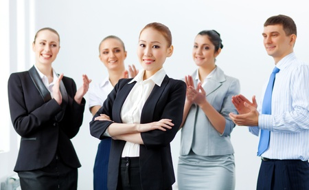 Young asian businesswoman smiling with colleagues applauding joyfully at background photo