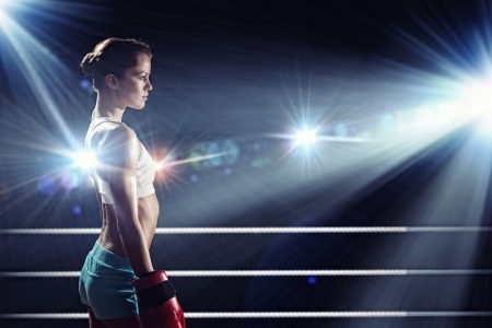 Young pretty boxer woman standing on ring photo