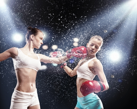 girl punch: Two young pretty women boxing standing against flashes background
