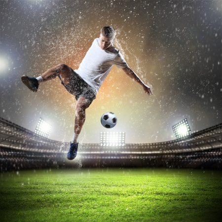 football player: Image of football player at stadium hitting ball