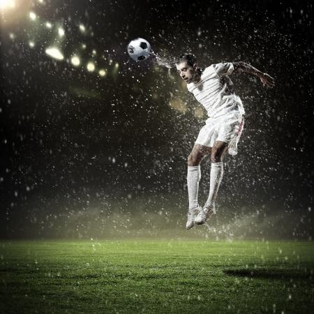 campo di calcio: Immagine del giocatore di calcio allo stadio che colpisce sfera Archivio Fotografico