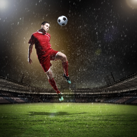Image of football player at stadium hitting ball photo