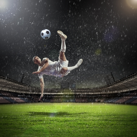 leisure sports: Image of football player at stadium hitting ball
