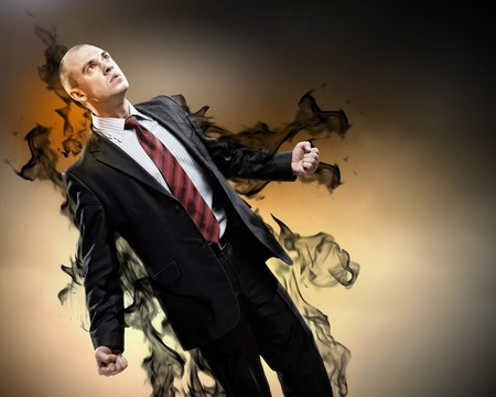 amok: Image of young businessman in anger standing in black smoke Stock Photo