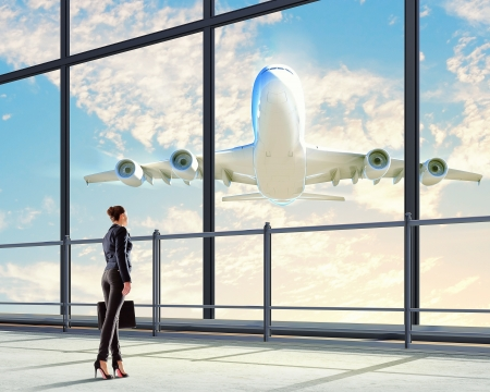 terminal: Image of businesswoman at airport looking at airplane taking off