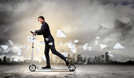 Image of young businessman in black suit riding scooter photo