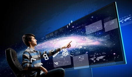 Young man in armchair pushing icon on media screen photo