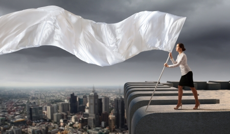 Image of attractive businesswoman holding white flag  Place for text photo
