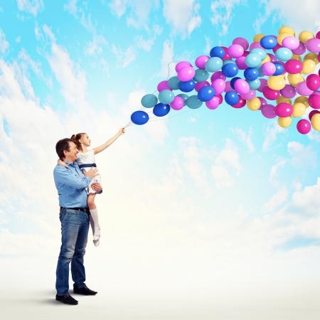 vater und baby: Bild der gl�cklichen Vater h�lt Tochter auf H�nden und Ballons Lizenzfreie Bilder