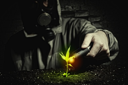 nuke plant: Young man in a protective suit touches to the sprout  post-nuclear future