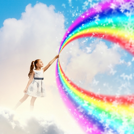 Image of little pretty girl drawing rainbow with finger photo