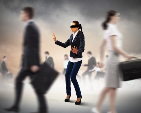 Image of businesswoman in blindfold walking among group of people photo