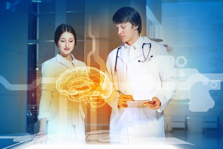 Image of two young doctors examining futuristic image of brain photo