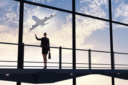 business travel: Image of businesswoman at airport looking at airplane taking off