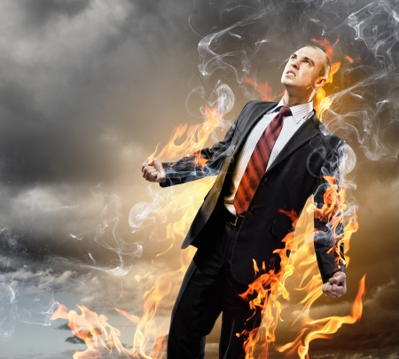 clenched: Image of young businessman in anger burning in fire Stock Photo