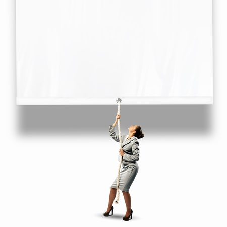 commercialism: Image of businesswoman pulling blank banner  Place for text