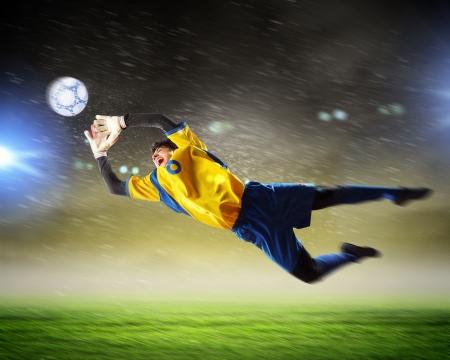 Gardien de but attrape le ballon Au stade, sous les projecteurs Banque d'images