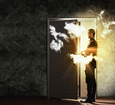Image of young businessman opening door with lights photo