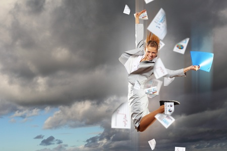Image of a businesswoman jumping high against financial background photo