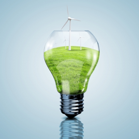 Electric light bulb and wind meels inside it as symbol of green energy photo