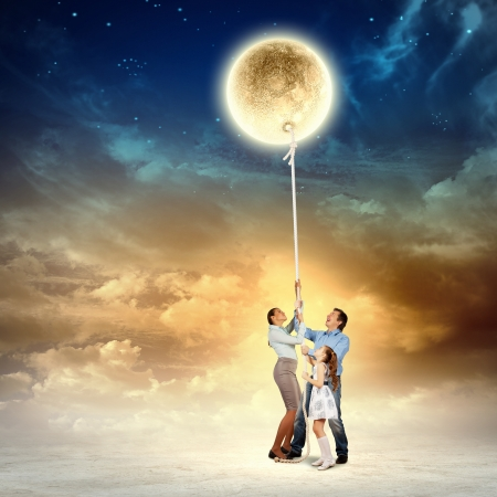Image of young happy family pulling moon photo