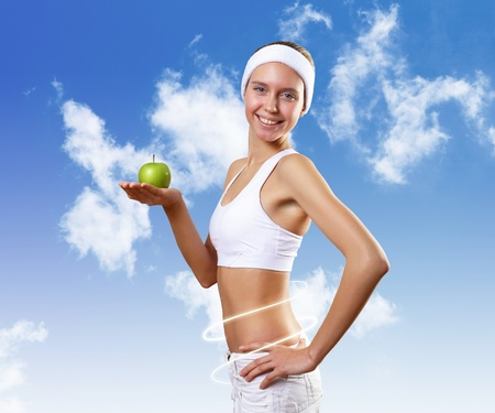 Portrait of a young woman doing sport with an apple photo