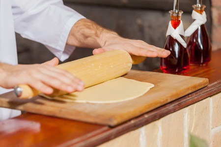 Close-up image of cook hands rolling out dough photo