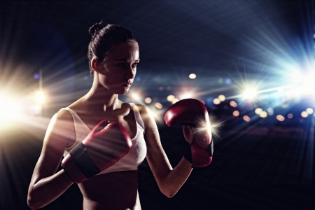 tough: Young pretty boxer woman standing in light flashes