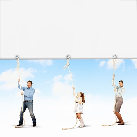 Image of young happy family pulling blank banner photo