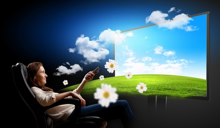 model home: Image of young woman in armchair watching 3d tv Stock Photo