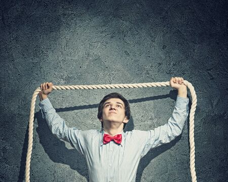 slave labor: Image of young aggressive businessman holding rope Stock Photo