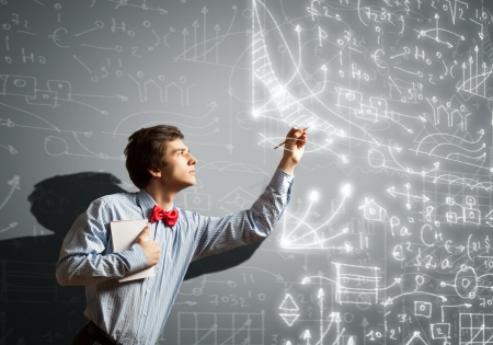 Image of thoughtful male student holding notebook in classroom photo