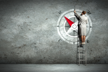 Businesswoman drawing compass with finger on wall standing on ladder photo