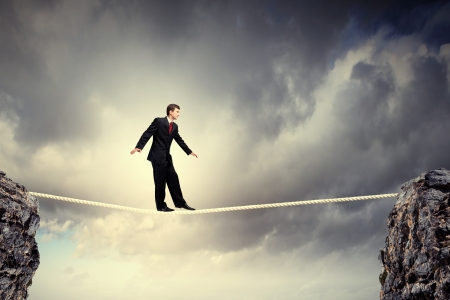 risky: Image of pretty businessman balancing on rope